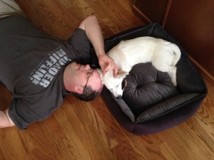 This is pretty much what she has to look forward to. It's a rough life, being our dog.  Photograph of a man lying on the floor next to a dog bed, snuggling with a small, white, dog.