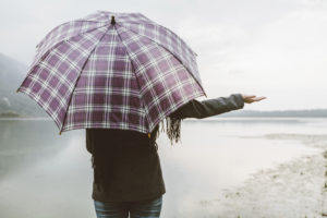 Woman standing, facing a beach, with a checkered umbrella unfolded over her shoulder and her hand out to the side checking for rain.