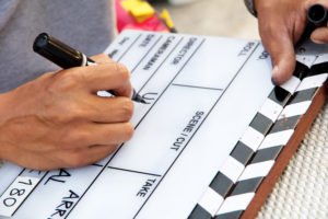 Picture of a hand writing on a slate used for marking a scene in a film or television production.