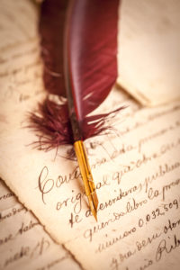 Image of a red quill upon a handwritten will on old parchment.