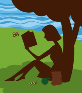 Silhouette of a woman sitting under a tree reading a book with her lunch sitting next to her.