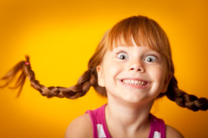 Image of a smiling red-haired girl with upward braids and a look of excitement!